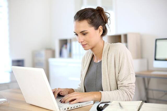 Attractive woman working in office on laptop.jpeg